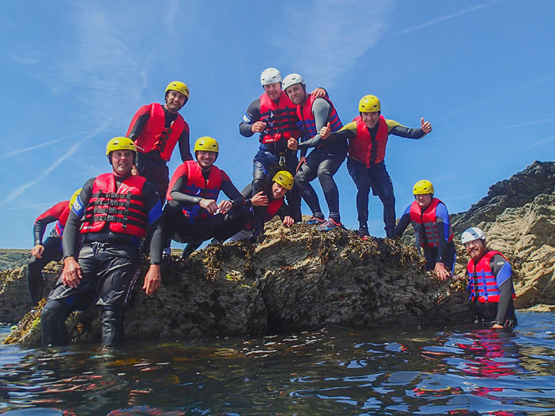 Large Coasteering stag do party taking a group photo upon a rocky outcrop