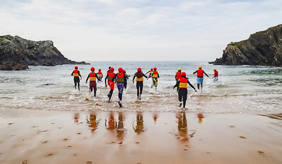 Large Coasteering group run into the sea at Porth Dafarch to acclimatize to the conditions