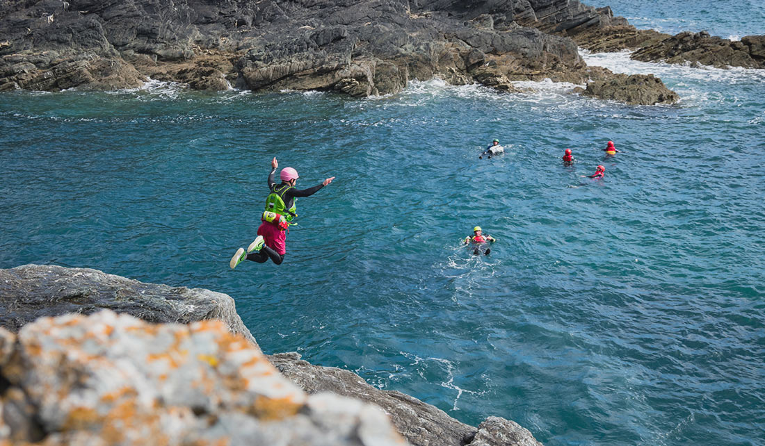 Man with pink helmet performs an epic Coasteering cliff jump into the sea below