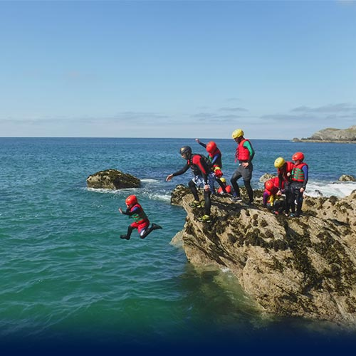 Little child take his first Coasteering jump into the sea